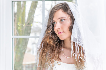 Closeup portrait of young female person, woman, bride in wedding dress, veil, shawl, face, pearl necklace, standing by window, white curtains, looking up, thinking