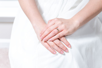 Closeup of hands of young female person, woman, bride in wedding dress, sitting by window, white curtains with engagement diamond ring on finger of hands