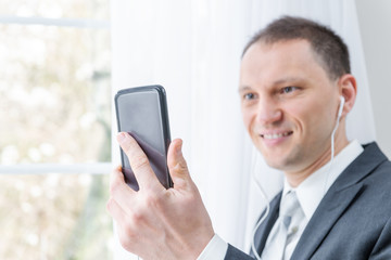 Closeup of young, happy man, male businessman in business suit, tie, standing by window in home, house room, white curtains, with earbuds headphones, holding phone, talking, video conference