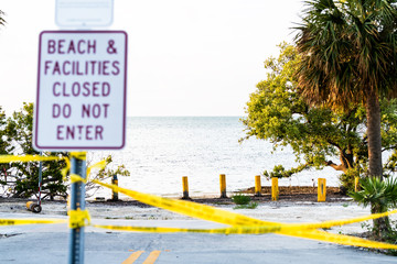 Beach, facilities closed, do not enter sign post by coast, shore after destruction of hurricane Irma with nobody, yellow tape, road in Islamorada key, Florida, palm trees