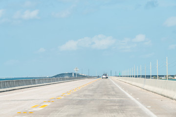 Point of view driving, moving in car on seven mile bridge landscape of Florida Keys water, atlantic ocean, cars on Overseas Highway US1 road, route