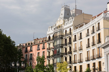 A view of Plaza De Oriente, at the centre of Madrid. The architecture is a mix of contemporary and old architecture. It is a large Square made by King Joseph 1. Lush green trees along with the blue