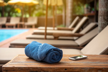 Holiday week end , relax concept,towel and smarthphone on wooden table near  bench pool villa beach side - Image