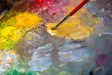 Paint brush on a paint palette with multicolor oil paint