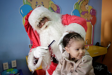 The owner of a kids hair salon, dressed as Santa Claus, combs the hair of a child in Monterrey