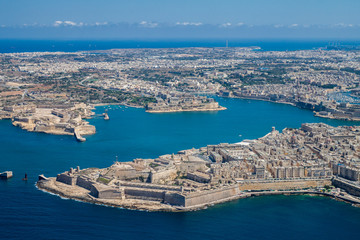 Malta aerial view. Valetta, capital city of Malta, Grand Harbour, Kalkara, Senglea and Vittoriosa towns, Fort Ricasoli and Fort Saint Elmo from above. Marsaxlokk city and Freeport in background