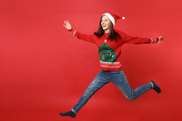 Smiling young Santa girl in knitted sweater Christmas hat jumping spreading hands and legs isolated on bright red background. Happy New Year 2019 celebration holiday party concept. Mock up copy space.