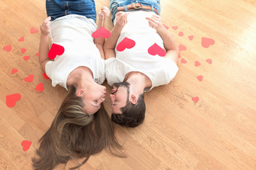 Young happy valentines couple lying on the floor and kissing