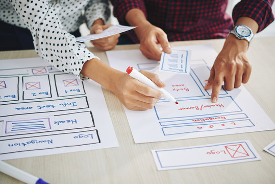 Hands of project managers working on interface design