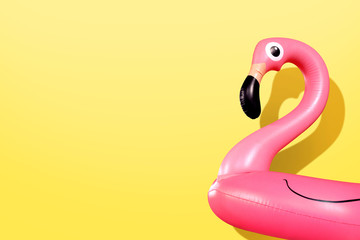 Poster Flamingo Giant inflatable Flamingo on a yellow background, pool float party, trendy summer concept