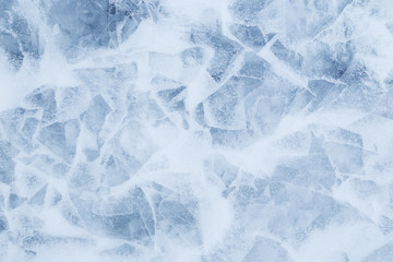 Close-up of snow on cracked and thin layers of ice in the winter. Simple and minimal full frame abstract background. Copy space.