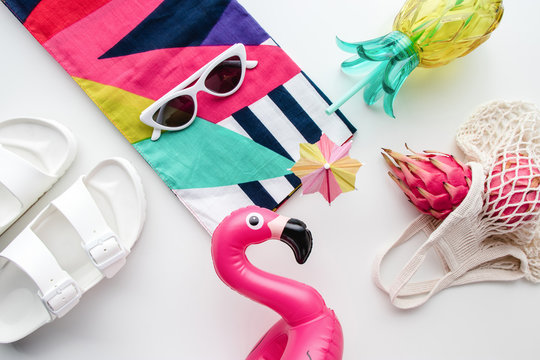 Flat lay of summer vibes concept with colorful travel fashion items, sunglasses, scarf, pink dragon fruit, flamingo inflatable drink holder, pineapple straw tumbler bottle, net bag and sandal on a whi