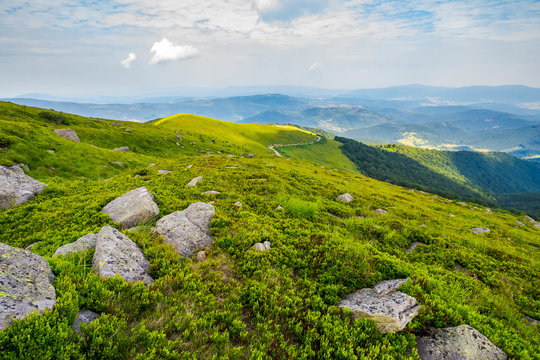 grassy slope with huge rocks. wonderful summer landscape in mountains. winding path through the distant hill. cloudy forenoon