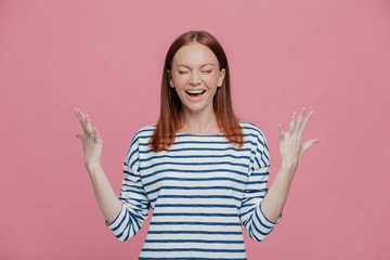 Excited overjoyed woman closes eyes, keeps hands raised, dressed in striped sweater, laughs positively, isolated over pink background. People, happiness, joy concept. Glad young female model