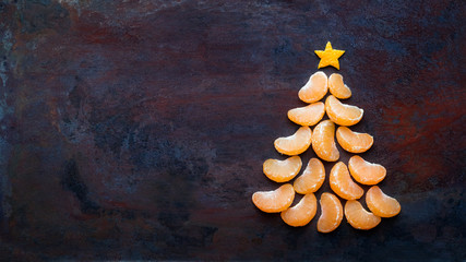 Tangerine christmas tree  on dark rust metal grunge background. Xmas festive greeting card with a tree of orange tangerine slices and star, copy space, flat lay