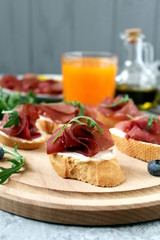 Canape or crostini with toasted baguette, cheese, bresaola and arugula on wooden board. Diet food. Iron on the food.