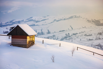 outskirts of the village on the hill. woodshed behind the wooden fence on a snowy slope. peaks of the distant mountain ridge in clouds. wonderful winter tale in gorgeous light
