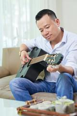 Smiling handsome Asian man enjoying playing guitar at home