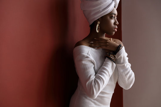 Beauty portrait of young woman dressed in white head tie, white sweater and big earrings, african bracelets. Dark red background.
