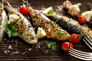 Fried fishes with addition of herbs, spices and lemon slices on a wooden background.