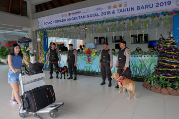 Indonesian policemen K-9 unit stand with dogs as they guard in front of arrivals terminal at I Gusti Ngurah Rai International Airport ahead of Christmas and New Year holiday in Bali