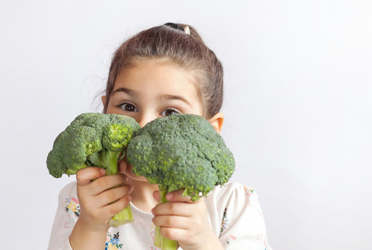 Happy smiling child girl eating vegetables. Healthy food. Fresh broccoli.