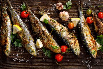 Grilled sardines with addition of fresh  herbs, lemon and spices on a wooden background, top view. Grilled seafood, barbecue
