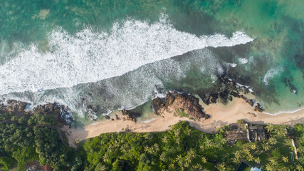 Aerial drone view of indian ocean on sunny tropical paradise island with aqua blue sea water