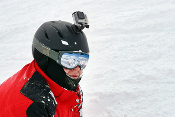 Snowboarder or skier portrait in sport goggles and protection helmet with mounted action camera and ski slope on background. Exreme winter sport outdoor activities