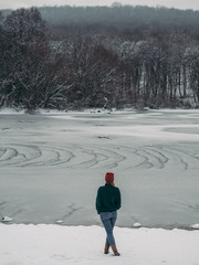 Rear view of traveler woman at frozen lake in forest.