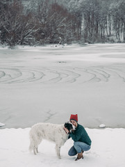 Woman with her dog at frozen lake. Winter landscape.