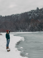 Woman on journey. Young woman having fun at frozen lake at wintertime in a forest.