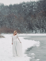 Bride stading outdoor at white nature. Winter wedding.