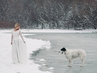 Bride stading outdoor at white nature. Borzoi dog follow bride at frozen lake.