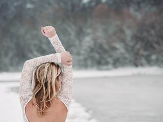 Rear view of woman in wedding dress outdoor. Winter fashion.
