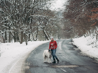 Woman walking with her dof at winter road in forest.