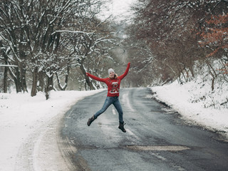 Woman having fun outdoor. Woman jumping on winter road through forest.