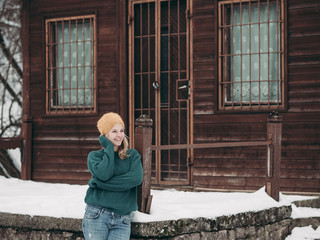 Woman at wooden cabin. Winter in forest.