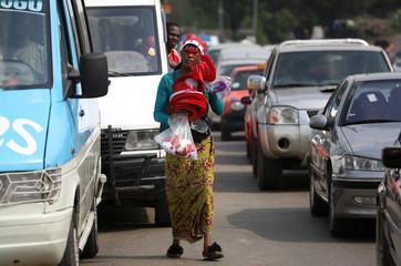 Street vendor, Fatim Kone, 25, wears Santa Claus' hat while selling Christmas items in Williamsville area of Abidjan