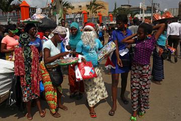 Street vendor, Kone Aicha, 27, wearing Santa Claus' hat and beard sells Christmas items in Adjame neighborhood in Abidjan