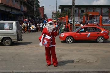 Street vendor, Nike Mawa, 20, dressed as Santa Claus, sells Christmas items in Adjame neighbourhood in Abidjan