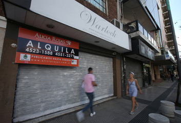 People walk past a sign of a real estate agent hanging from a closed shop, in Buenos Aires