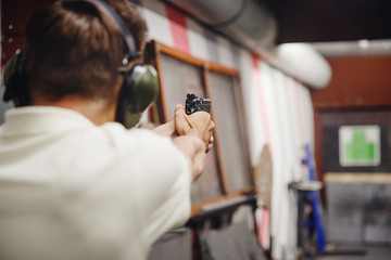 Shooting range gun. Man shoots pistol in noise protection headphones