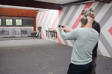 Shooting training. Man shoots from aim gun in paper target