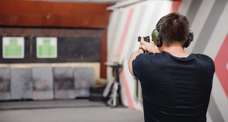 Man directs firearm gun pistol at target firing range or shooting range