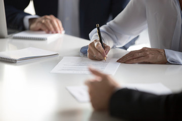 Businesspeople gathered together at business meeting after successful negotiations ready to sign agreement official paper close up focus on businesswoman hands holds pen affirm contract with signature