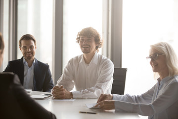 Wall Mural - Positive millennial well-dressed businessmen middle aged attractive businesswoman sitting around the office table during negotiations or conference having pleasant conversation with business partners