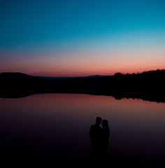 Silhouette of young couple on background of sunset.