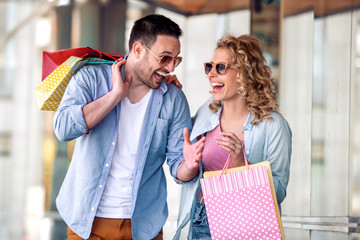 Portrait of a couple with shopping bags in city