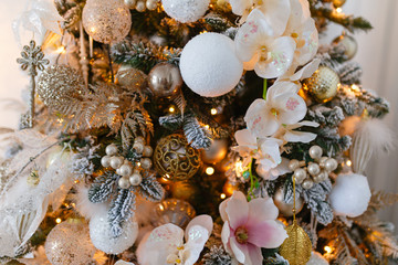 Gold decorations Christmas toys on the Christmas tree. Garland with bright yellow lights in artificial snow.